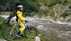 Biker by a torrent on Mount Linas
